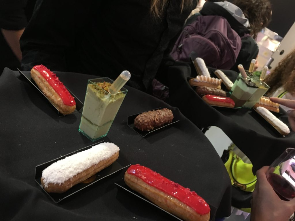 trays of dessert at mini cakes at server with eclair at eclair at macaron at blueberry cheesecake at summer rendezvous at dj at delysee french pastries